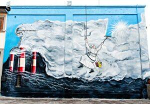 une illustration dessinée sur un mur à l'extérieur d'un building montrant le pape qui repeint le ciel pour effacer la pollution sortant d'une usine.