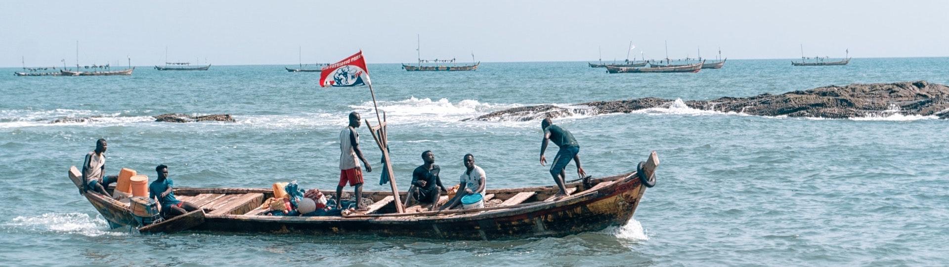 pecheurs sun un bateau en bois, faisant voler un drapeau.